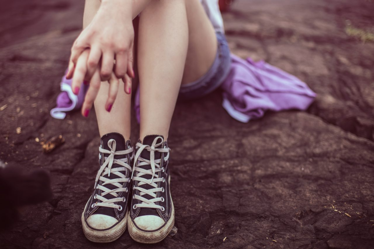 Young woman pictures sitting on rocky ground, wearing converse sneakers and photo is cropped below her knees.