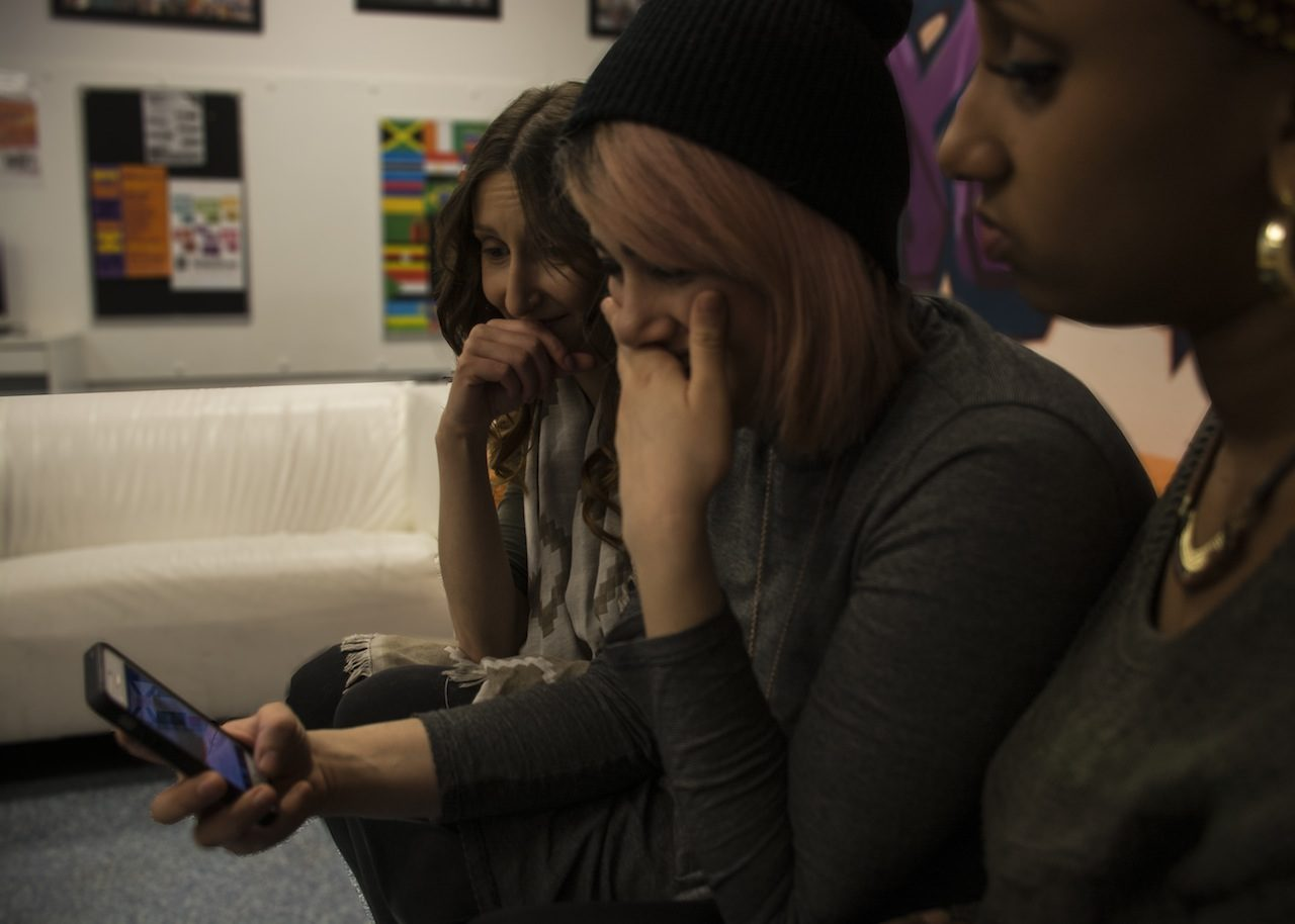 Photo of three diverse women looking at a phone and laughing at an image.