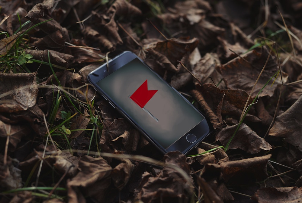A phone abandoned in a pile of leaves depicts a red flag on the screen.