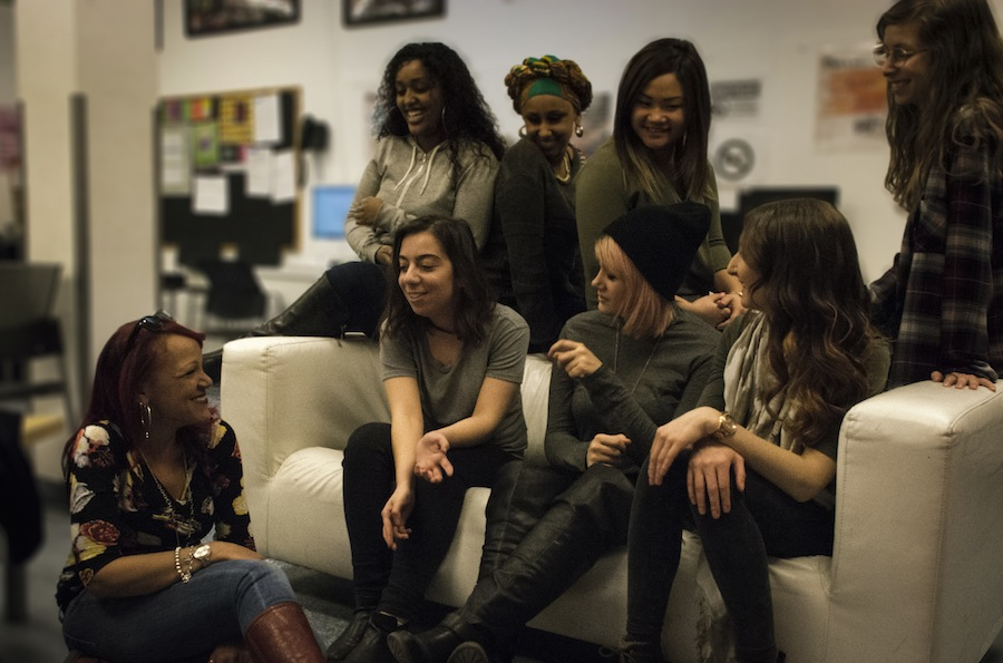 Diverse group of young women together sat together and sharing a moment of conversation.