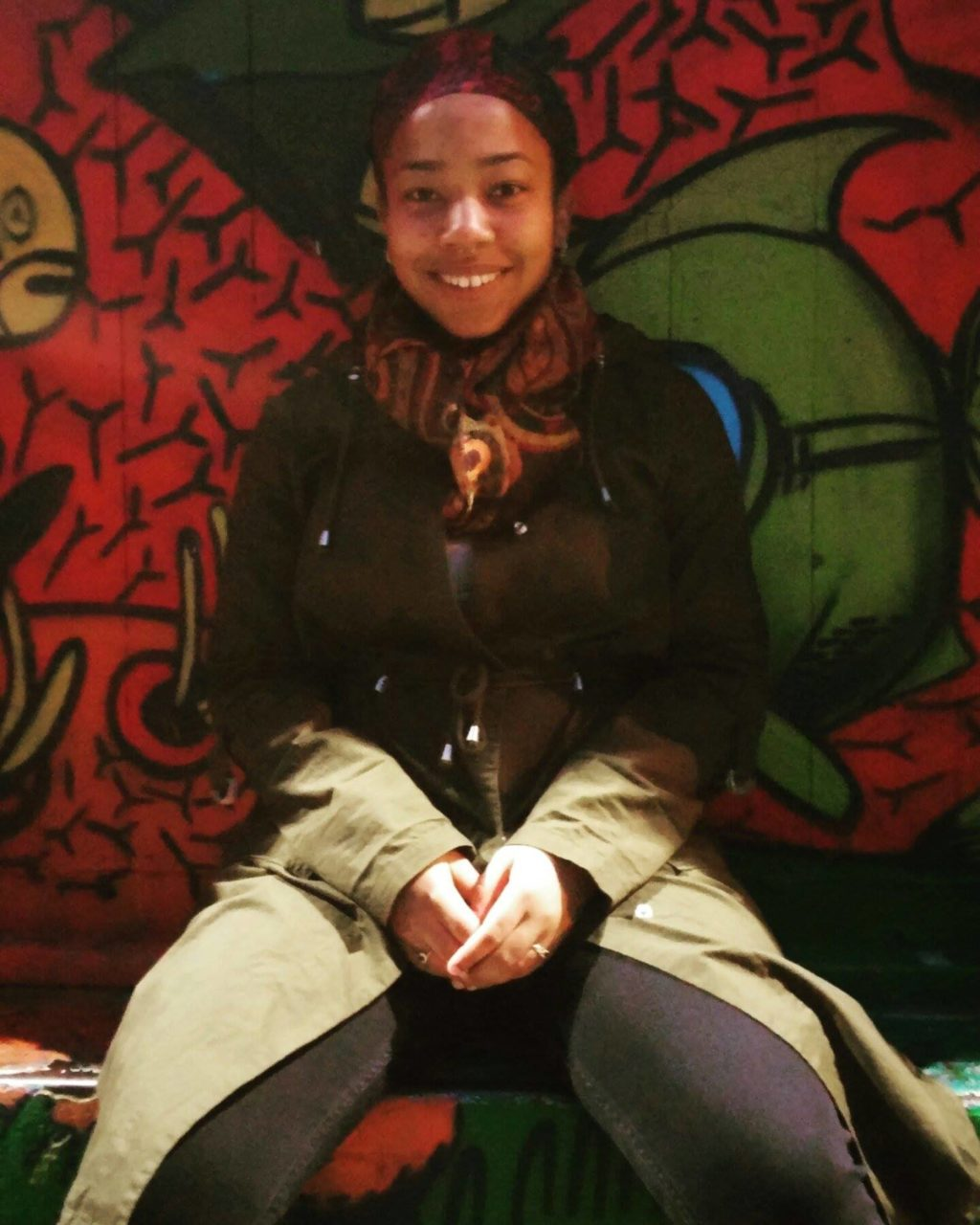 Jade posed and smiling in front of a graffiti wall.