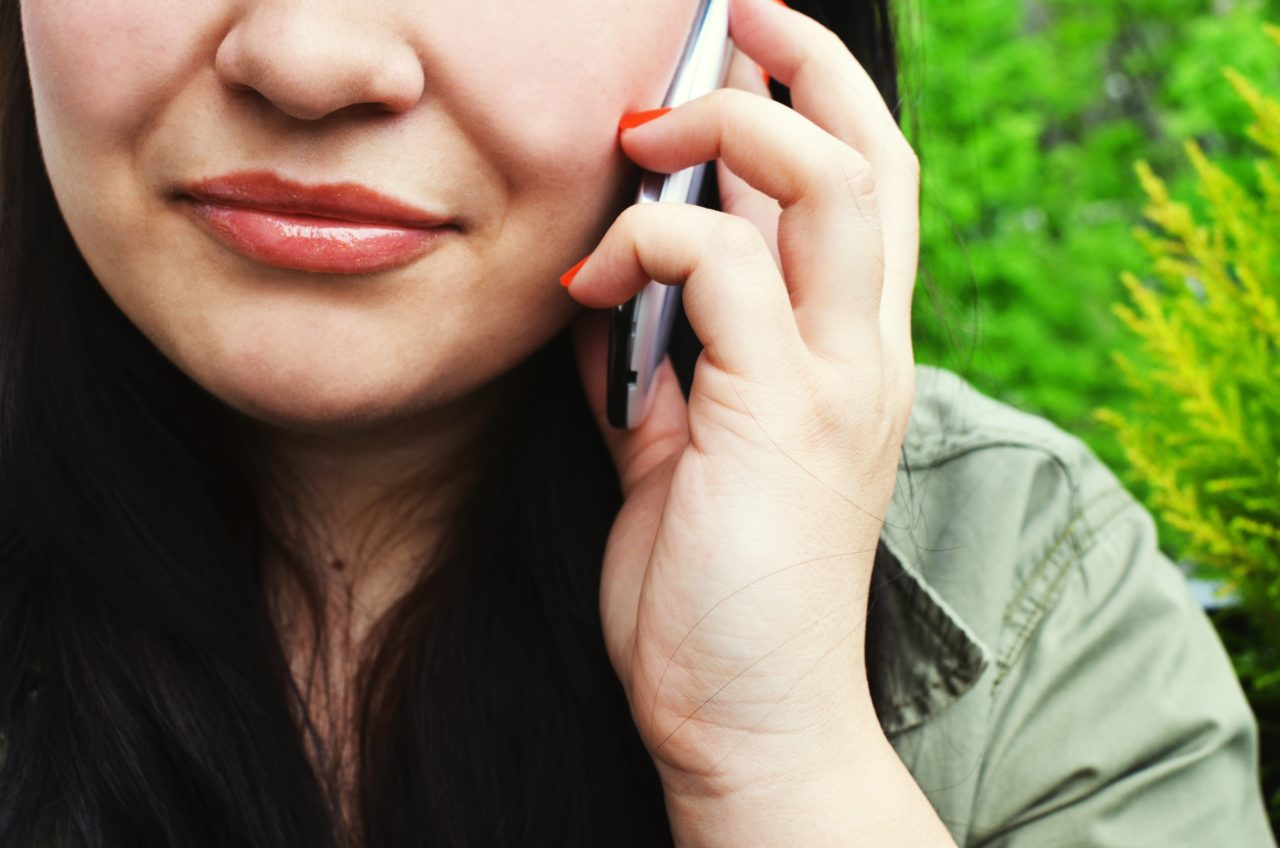 Young woman on phone, image is cropped at her nose, mouth and hand holding phone with a green leafy bush-like background.