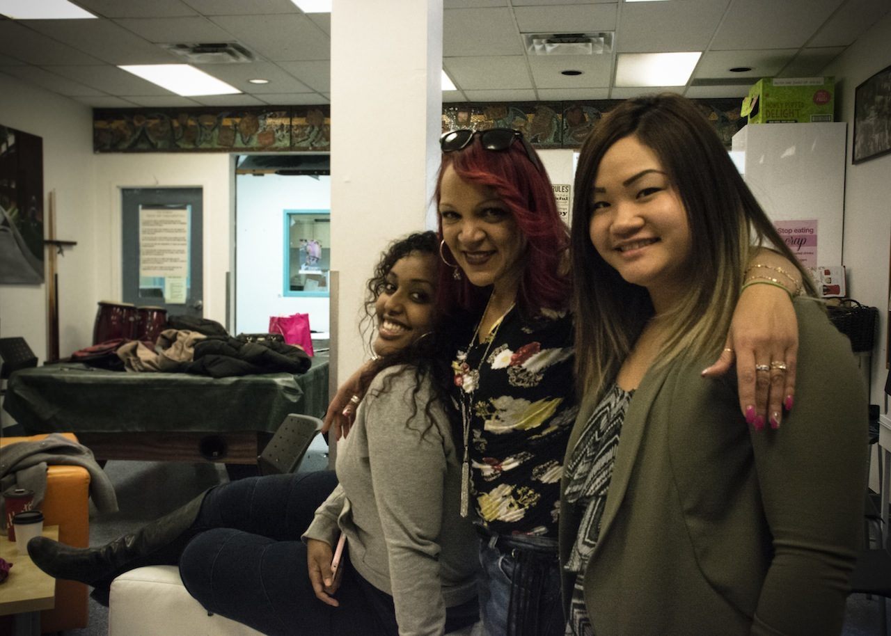 Diverse group of three women embracing and smiling at camera.