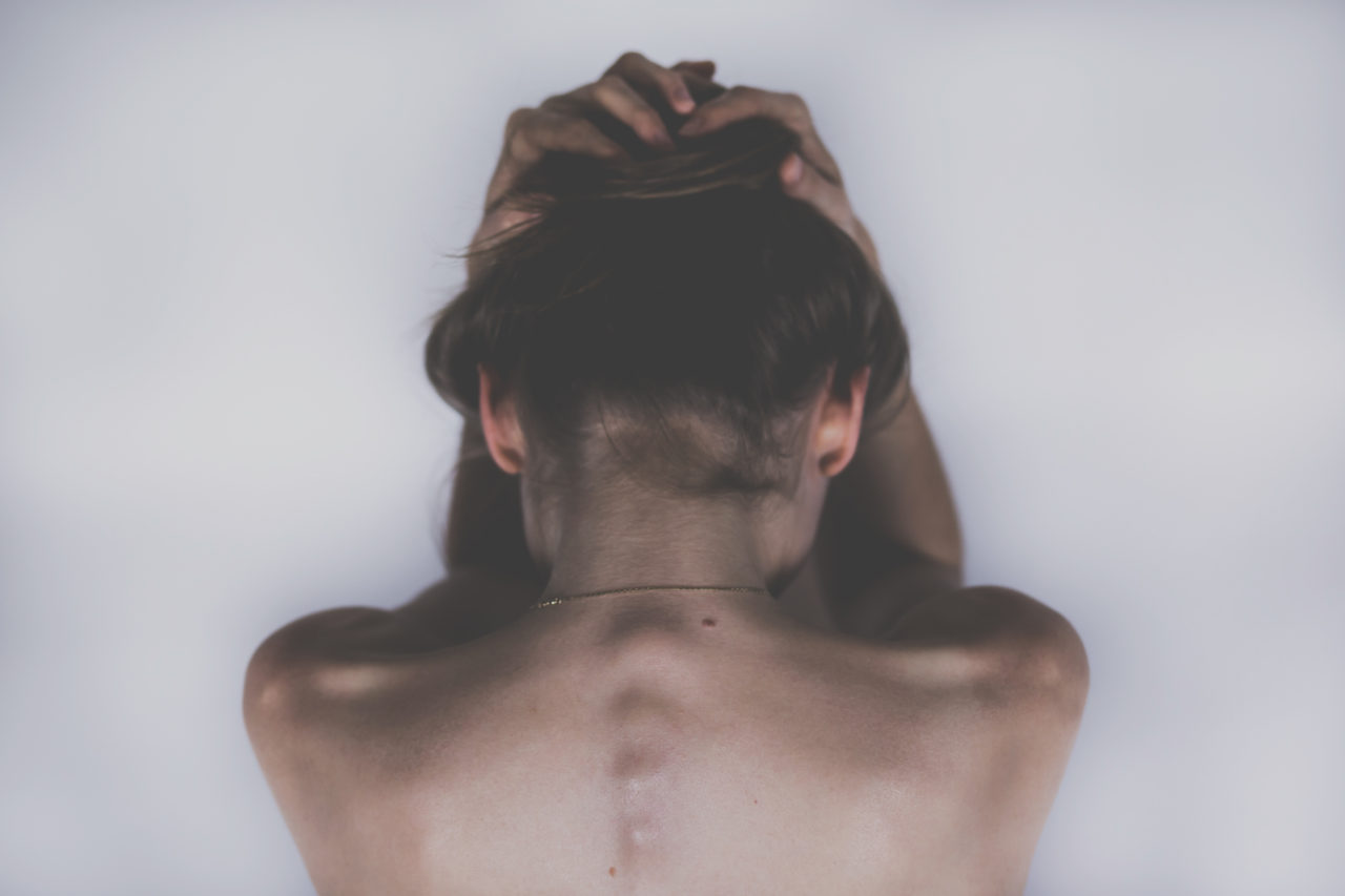 A woman crouches over with her hands above her head and her back exposed.